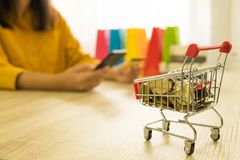 Money in a trolley on table, background women holding credit ca stock photo