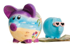 Money Between Two Piggy Banks. Two isolated piggy banks with some money between them Royalty Free Stock Image