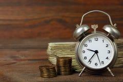 Money. The Ukrainian hryvnia near clockwork alarm clock on wooden background Royalty Free Stock Images