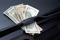 Money under windshield wiper. Money stuck under a windshield wiper symbolizing car expenses Stock Photography