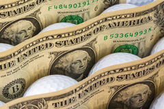 Money and US dollars banknotes. Dollars banknotes and white golf balls in open box in a shop royalty free stock image