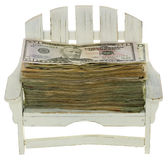 Money for Vacation. Big Stack of US Currency Fifity Dollar Bills lying in a miniature white adirondack chair,  isolated on white background Royalty Free Stock Images
