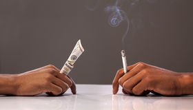 Money vs cigarette Stock Photo