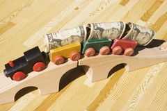 Money wagons. A toy train pulling a cargo of money and going over a bridge.  This picture could be a reference to 'bridging loan','money delivery', gravy train Royalty Free Stock Images