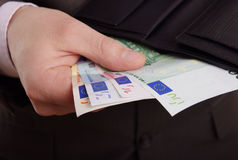 Money and wallet. A suited man taking money out of his black leather wallet Royalty Free Stock Photo