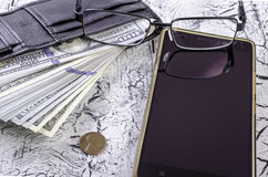 Money in wallet, glasses and a smartphone. Royalty Free Stock Image