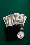 Money in wallet and stopwatch Stock Photo