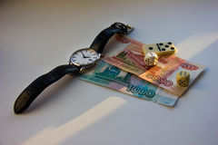 Money, watch, dice and domino. Beam of light falls on the money ruble, dice, watch, domino. Royalty Free Stock Image