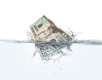 Money on water. Stock image of Twenty dollar bill splashing into water over white  background, very detailed splash Stock Photography