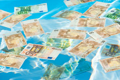 Money in water, floating and sinking. Close-up shot of Euros Stock Photography