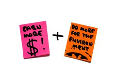 Money, wealth, economy versus environment, earth, responsibility. post it notes. To post it notes on whiteboard. One saying Earn more money, the other one Royalty Free Stock Image