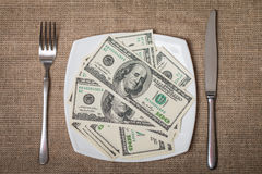Money on a white plate with knife and fork Royalty Free Stock Image