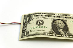 Money wired. One dollar bill with an electrical wire coming from Stock Image