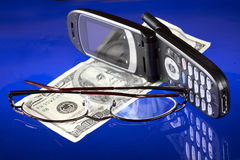 Money,wireless phone & eyeglasses. Selectively focused studio still-life on a blue background Stock Photos