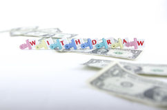 MONEY AND WITHDRAW LETTER PIECES. Letter pieces forming the word withdraw in colorful clips with scattered dollar bills Royalty Free Stock Image