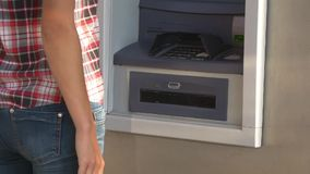 Money withdrawal from ATM. Young woman presses enter in ATM keypad, removes credit card and takes money, cash withdrawal and checking account balance stock footage