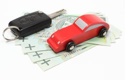 Money, wooden red toy car and key vehicle. White background Stock Photo