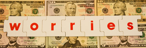 Money  worries. A macro image of the wod worries in bold red lower case text on a series of Dollar bills of different denominations Stock Image