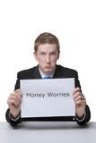 Money worries and problems. Business man holding a paper sign with the words money worries written on it looking unhappy Stock Image
