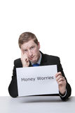 Money worries and problems. Business man holding a paper sign with the words money worries written on it looking unhappy Royalty Free Stock Photo