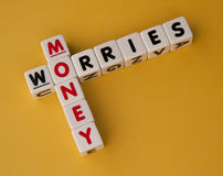 Money worries. Text ' money ' and ' worries ' inscribed on small white cubes and arranged crossword style with common letter Stock Photography