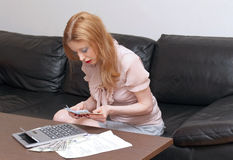 Money worries. Young woman counting money and calculating home budget with calculator Royalty Free Stock Images