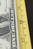 Money worth. Us dollar bill with measure tape concept metaphor for measuring money's worth. Economy investment royalty free stock image