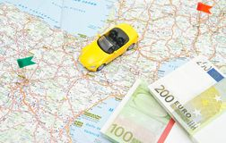 Money and yellow car on map Royalty Free Stock Images