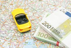 Money and yellow sport car on map Stock Images