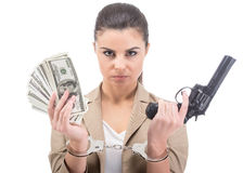 Money. Young woman is holding in hand a lot american dollars and gun isolated on white background. A handcuffs on her hands Stock Photos