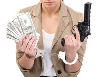 Money. Young woman is holding in hand a lot american dollars and gun isolated on white background. A handcuffs on her hands Royalty Free Stock Photos