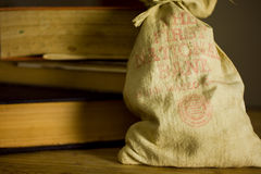 """Antique Moneybag & Books. An antique moneybag sitting next to worn vintage tomes, with faded letters reading """"The First National Bank of San Mateo&#x22 Royalty Free Stock Photo"""