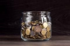 Moneybox с золотом и серебряными монетами на деревянной предпосылке Стоковые Изображения