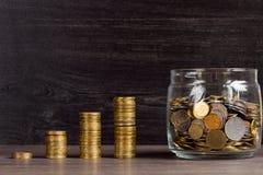 Moneybox с золотыми монетками на деревянной предпосылке Стоковые Изображения RF