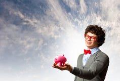 拿着moneybox的年轻商人 免版税库存照片