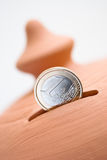 Moneybox. One euro coin in the slot of a moneybox Stock Photos