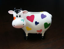 Moneybox as a cow with painted hearts. On a wooden table Royalty Free Stock Photos