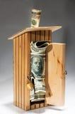 Moneybox di legno in pieno di soldi Immagine Stock