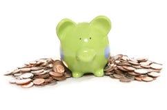 Moneybox do banco Piggy com as moedas britânicas da moeda Fotos de Stock Royalty Free