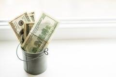 Moneybox dollar i hink på det vita fönstret Ljus bakgrund placera text Top beskådar mycket pengar fotografering för bildbyråer