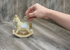 Moneybox in the form of a horse. Located on wooden background Stock Photos