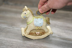 Moneybox in the form of a horse. Located on wooden background Royalty Free Stock Image