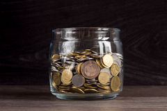 Moneybox with gold and silver coins on wooden background Stock Images