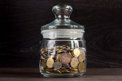 Moneybox with gold and silver coins on wooden background Royalty Free Stock Photo