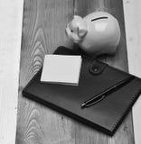Moneybox med svinframsidan nära organisatör och penna Arkivbilder