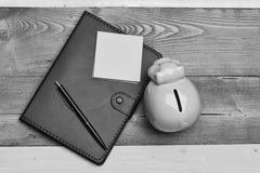 Moneybox med svinframsidan nära organisatör och penna Royaltyfri Bild
