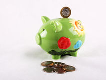 Moneybox pig. Green moneybox piggy and some coins near it Royalty Free Stock Images