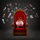 Moneybox pig in crown on the royal throne. In the room with falling euro banknotes Royalty Free Stock Photo