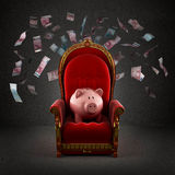 Moneybox pig on the royal throne. In the room with falling euro banknotes Stock Photos