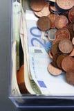 Moneybox plástico con las monedas y la opinión euro de papel de la moneda desde arriba imagen de archivo libre de regalías